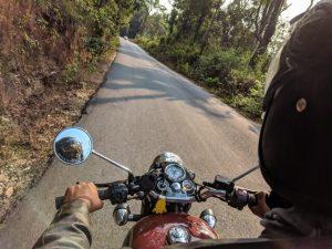 Mies ajaa moottoripyörää kesällä